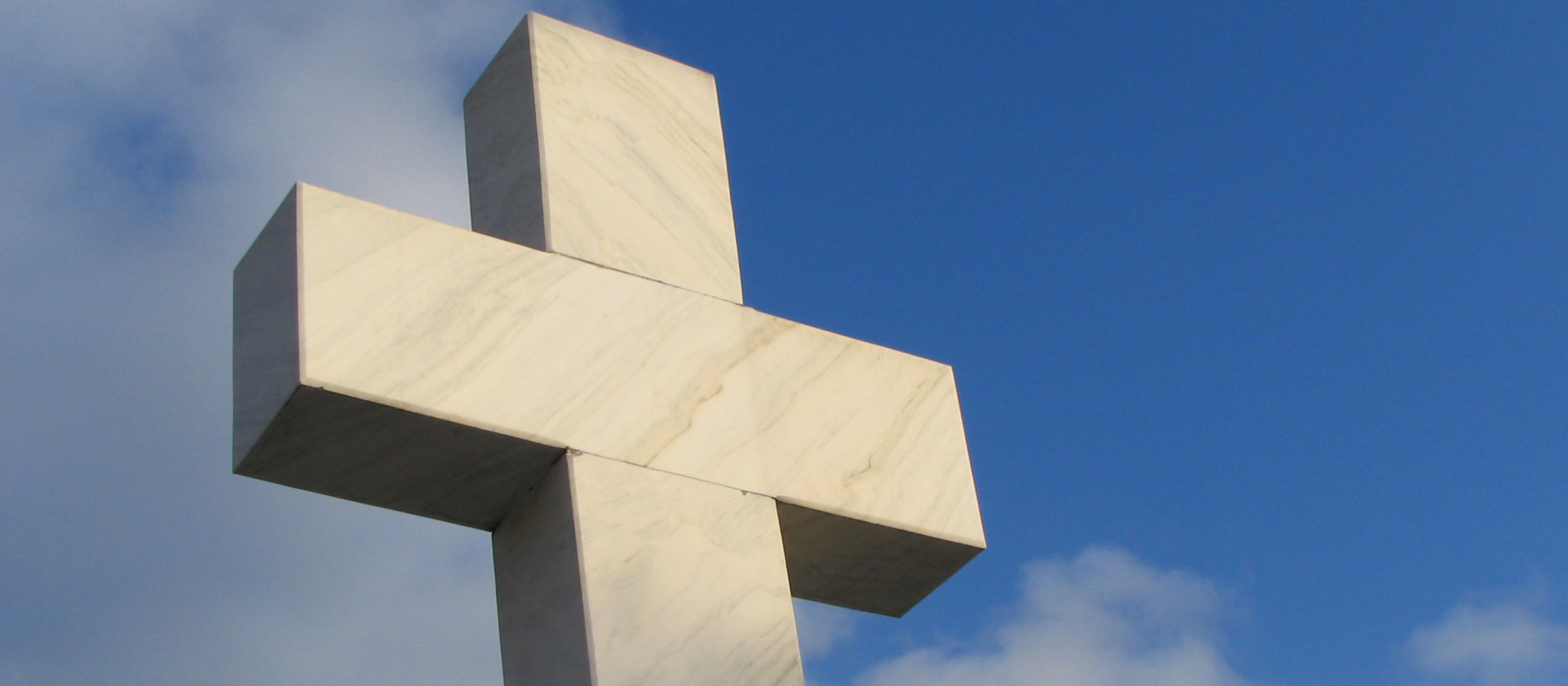 Large cross monument/statue erected outside.